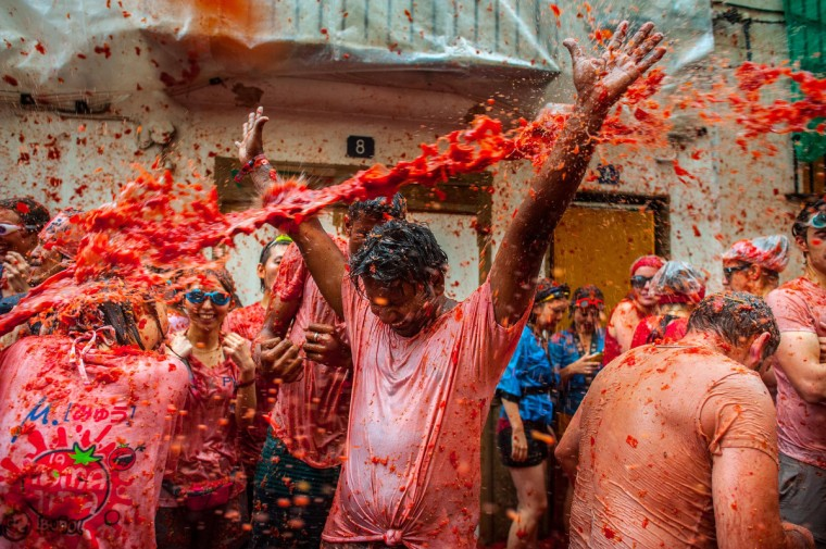 Revellers celebrate covered by tomato pulp while participating the annual Tomatina festival on August 28, 2013 in Bunol, Spain. An estimated 20,000 people threw 130 tons of ripe tomatoes in the world's biggest tomato fight held annually in this Spanish Mediterranean town. (David Ramos/Getty Images)