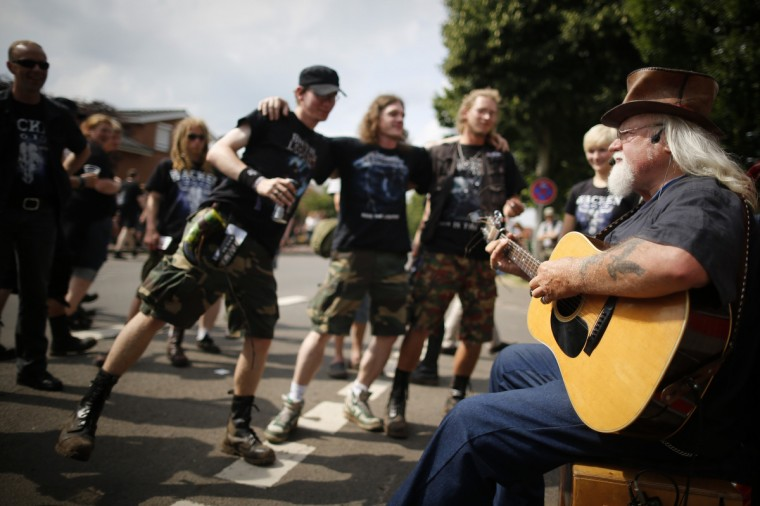 People dance as a man plays a guitar during the Wacken Open Air Festival 2013 in Wacken, Germany. (Philipp Guelland/Getty Images)