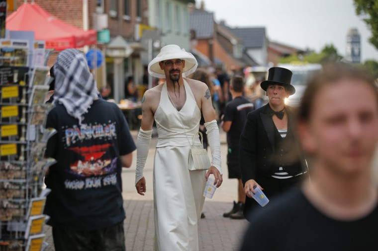 Christian (L) and Bodil, dressed up as bride and groom, walk along the village's main street during the Wacken Open Air Festival 2013 in Wacken, Germany. (Philipp Guelland/Getty Images)