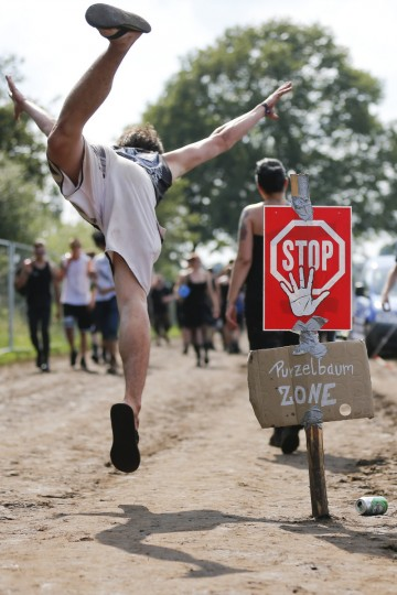 "A participant of the 24th heavy metal Wacken Open Air (WOA) Festival 2013 in Wacken, northern Germany makes a somersault next to a sign reading ""Stop - Purzelbaum-Zone"" ( stop-somersault-zone). (Philipp Guelland/Getty Images)"