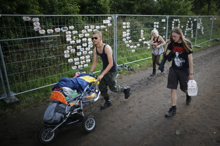 Participants of the 24th heavy metal Wacken Open Air (WOA) Festival 2013 in Wacken, northern Germany walk next to a fence showing the Wacken logo composed of empty beer cans. (Philipp Guelland/Getty Images)