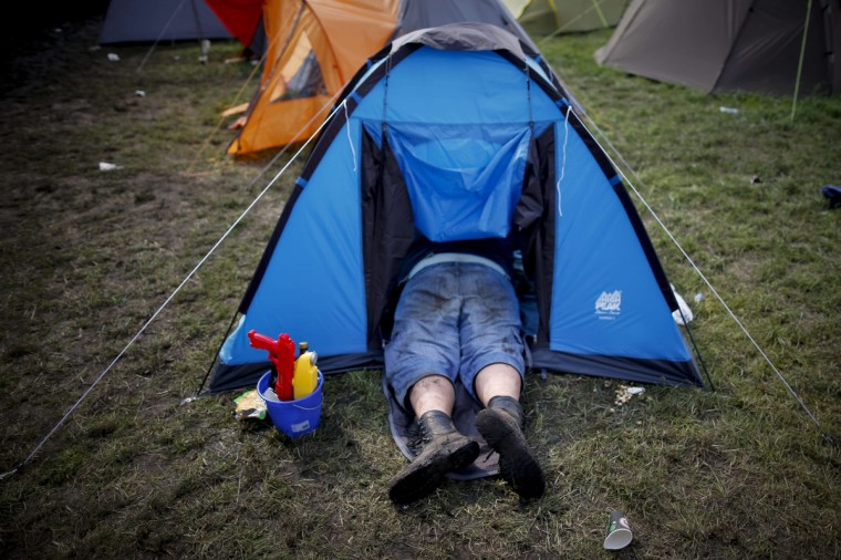 A participant of the 24th heavy metal Wacken Open Air (WOA) Festival 2013 is pictured as he lies in a tent on a campsite in Wacken, northern Germany. (Philipp Guelland/Getty Images)