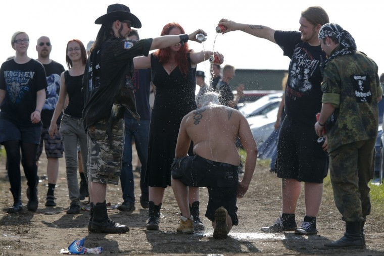 "Revellers ""baptize"" a friend for his first trip to the festival during the 24th heavy metal Wacken Open Air (WOA) Festival 2013 in Wacken, northern Germany. (Philipp Guelland/Getty Images)"