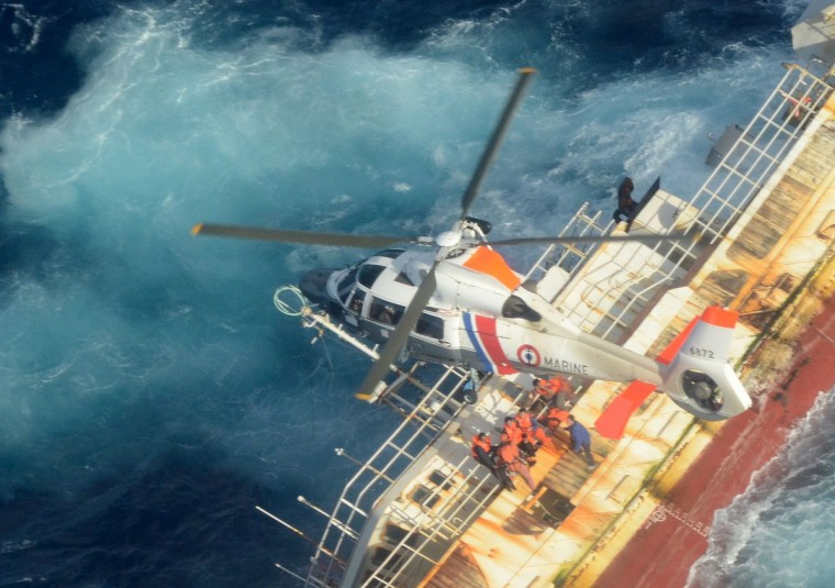 A helicopter hovers over a sinking Chinese fishing vessel at sea off the coast of French Polynesia. At least four sailors have died missing after a Chinese fishing trawler sunk off the coast of Rapa island in French Polynesia, officials said. (Getty Images)