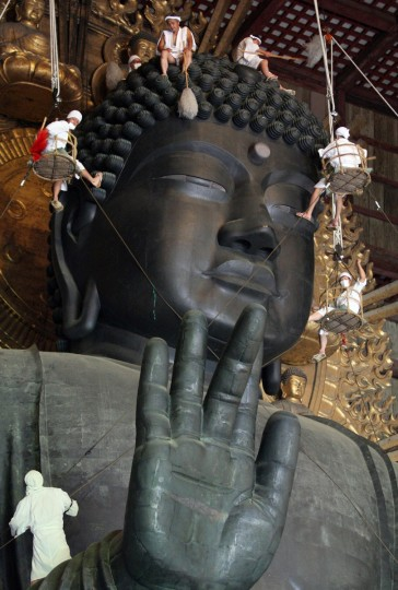 Some 150 Buddhist monks and believers in white costumes wipe and sweep the 15-meter-tall Great Buddha statue which was built in 752 AD, at Todaiji Temple in Nara, western Japan. Monks and volunteers cleaned a year's worth of grime from the Great Buddha for the annual sprucing up as the rirual cleaning. (Jiji Press/Getty Images)