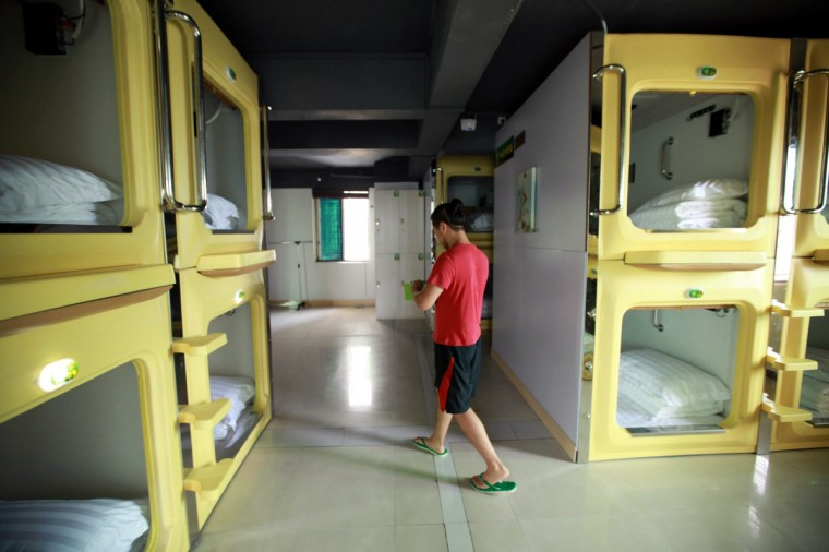 A guest walks in a newly opened capsule hotel in Haikou, south China's Hainan province on August 13, 2013. The capsules are the length and width of no more than a single bed and equipped with ventilating fans, flat-panel televisions and foldable tables. (Getty Images)