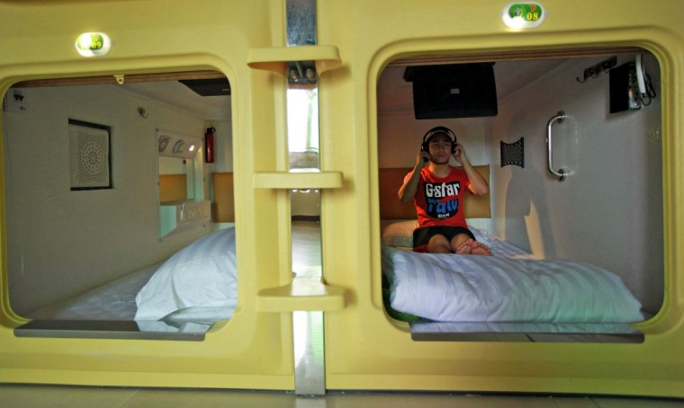 A guest lies in his capsule in a newly opened capsule hotel in Haikou, south China's Hainan province on August 13, 2013. The capsules are the length and width of no more than a single bed and equipped with ventilating fans, flat-panel televisions and foldable tables. (Getty Images)
