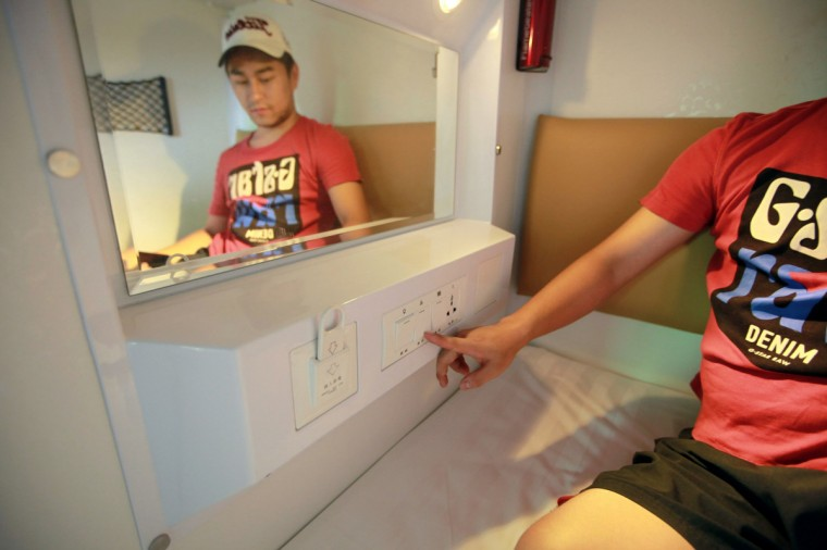 A guest turns on the light in his capsule in a newly opened capsule hotel in Haikou, south China's Hainan province on August 13, 2013. The capsules are the length and width of no more than a single bed and equipped with ventilating fans, flat-panel televisions and foldable tables. (Getty Images)
