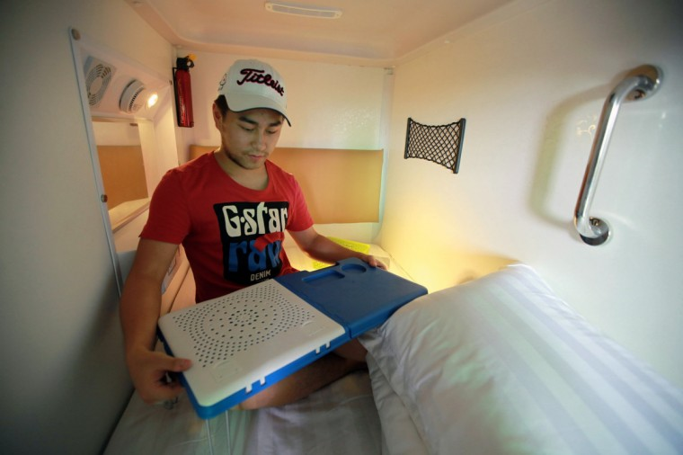 A guest unfolds a table in his capsule in a newly opened capsule hotel in Haikou, south China's Hainan province on August 13, 2013. The capsules are the length and width of no more than a single bed and equipped with ventilating fans, flat-panel televisions and foldable tables. (Getty Images)