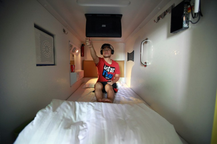 A guest watches TV in his capsule in a newly opened capsule hotel in Haikou, south China's Hainan province on August 13, 2013. The capsules are the length and width of no more than a single bed and equipped with ventilating fans, flat-panel televisions and foldable tables. (Getty Images)
