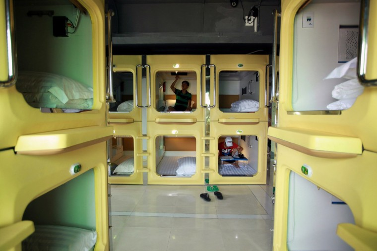 Guests are seen relaxing in their capsules in a newly opened capsule hotel in Haikou, south China's Hainan province on August 13, 2013. The capsules are the length and width of no more than a single bed and equipped with ventilating fans, flat-panel televisions and foldable tables. (Getty Images)