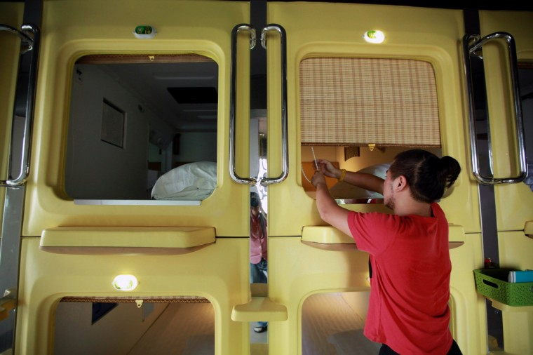 A guest pulls the curtain of his capsule in a newly opened capsule hotel in Haikou, south China's Hainan province on August 13, 2013. The capsules are the length and width of no more than a single bed and equipped with ventilating fans, flat-panel televisions and foldable tables. (Getty Images)