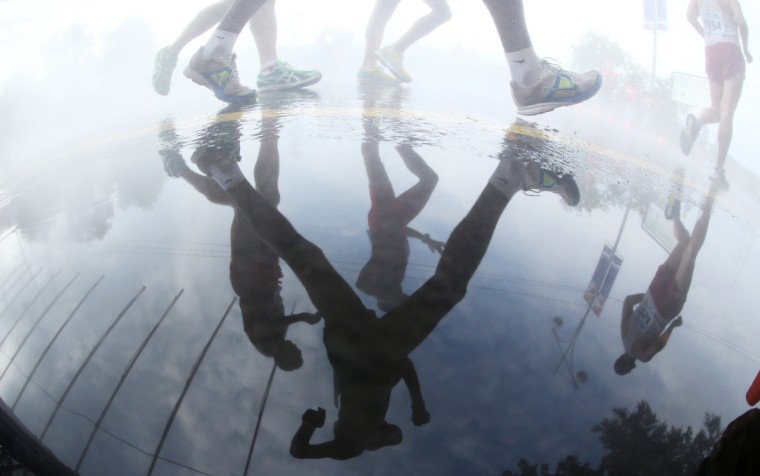 Athletes are reflected in a puddle as they compete in the men's 50 kilometres walk final at the 2013 IAAF World Championships at the Luzhniki stadium in Moscow. (Kirill Kudryavtsev/Getty Images)