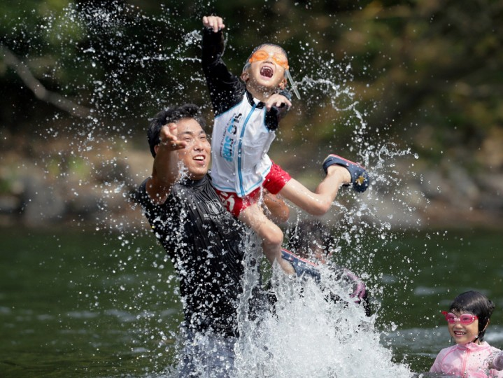 Family members play in the river at Shimanto city in Kochi prefecture . Japan's record high temperature of 41 degree Celsius was registered at Shimanto, a Pacific coast city on the southern island of Shikoku on August 12. (Jiji Press/Getty Images)