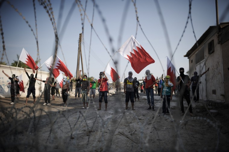 Bahraini protestors wave their national flag as they stand behind barbed wire placed by riot police during demonstration against the ruling regime in the village of Shakhora, west of Manama. (Mohammed Al-Shaikh/Getty Images)