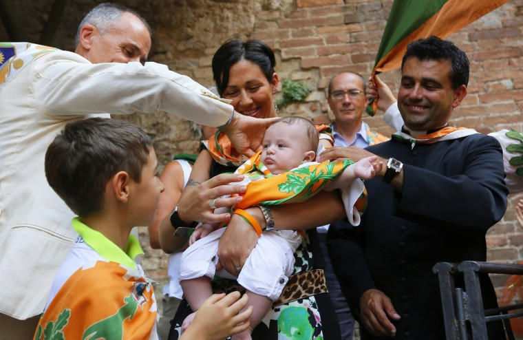 Priest Francesco Rinaldi (L) baptizes a child as a new member of the Contrada of Forest on August 15, 2013. The Palio of Siena race (known locally simply as Il Palio) is held twice a year in the Tuscan city of Siena, in which jockeys ride bareback around a makeshift race course set up in the city's central square. (Fabio Muzzi/Getty Images)