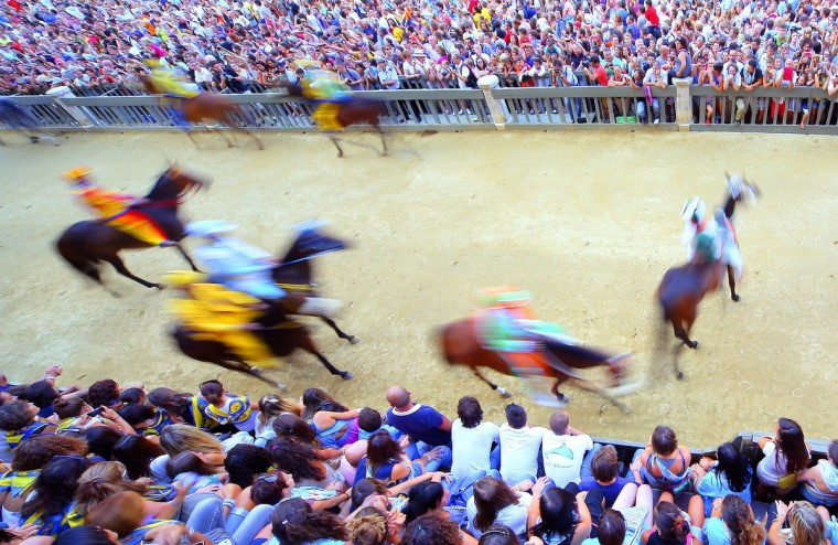 Riders take part in a practice race a day before the Palio di Siena horse race in Siena on August 15, 2013. (Fabio Muzzi/Getty Images)