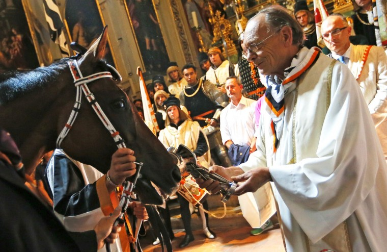 "A horse is blessed by a priest of the Contrada de ""Lupa"" (She-Wolf) before the Palio di Siena horse race in Siena on August 16, 2013. The Palio di Siena (known locally simply as Il Palio), is a horse race held twice a year in the Tuscan city of Siena, in which jockeys ride bareback around a makeshift race course set up in the city's central square. (Fabio Muzzi/Getty Images)"