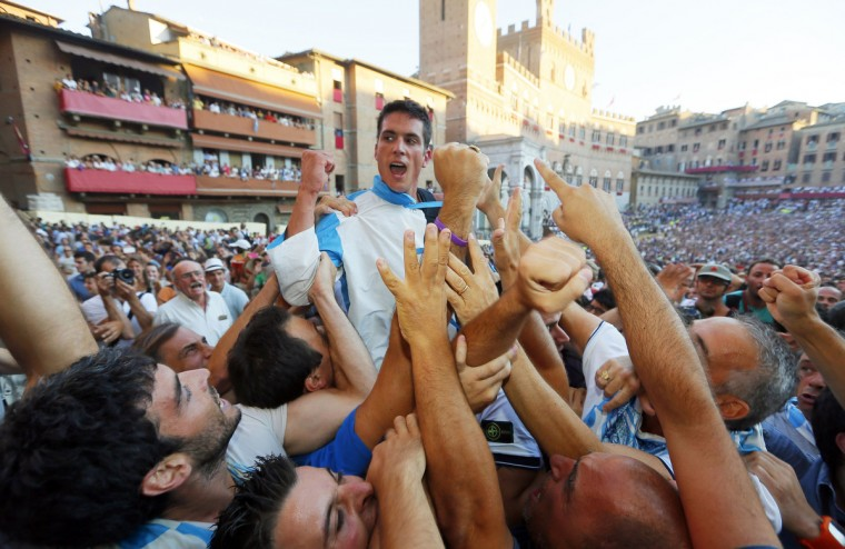 Supporters of the Contrada of Wave congratulate the rider Giovanni Atzeni after winning the Palio horse race in Siena on August 16, 2013. (Fabio Muzzi/Getty Images)