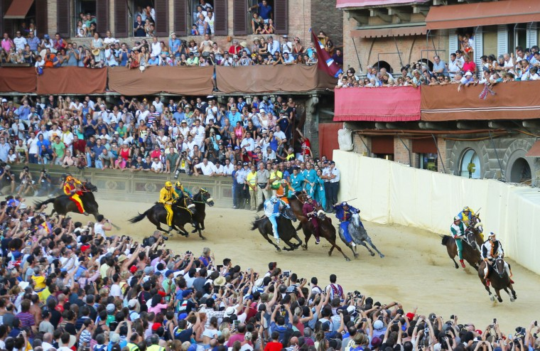 Riders compete in the Palio horse race in Siena on August 16, 2013. The Palio medieval race is held twice a year in Siena with jockeys riding bareback around a makeshift race course set up in the city's central square. (Fabio Muzzi/Getty Images)