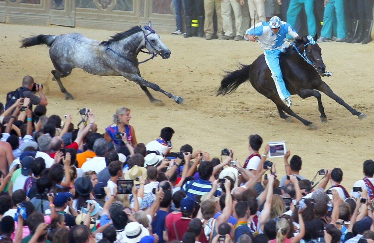 Rider of Contrada of Wave Giovanni Atzeni (R) passes the horse of Contrada of Shell to win the Palio horse race in Siena on August 16, 2013. (Fabio Muzzi/Getty Images)