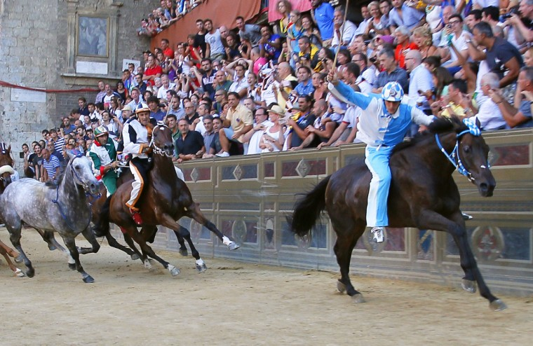 Rider of the Contrada of Wave Giovanni Tittia (R) wins the Palio horse race in Siena on August 16, 2013. (Fabio Muzzi/Getty Images)