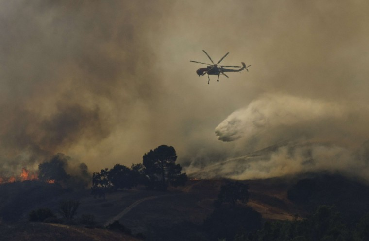 A fire helicopter dumps water on a brush fire near Highway 101 and Calabasas on August 18, 2013 north of Los Angeles, California. A car fire sparked a brush fire off the northbound 101 Freeway in Calabasas on Sunday. LA County Fire says the blaze has burned between 40 to 50 acres. Crews are battling flames from the ground and air. (Joe Klamar/Getty Images)