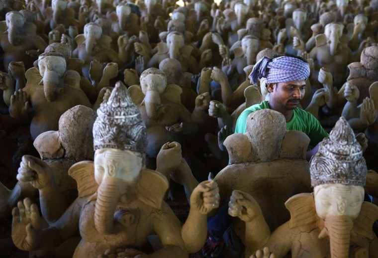 An Indian worker works on eco-friendly figures of Hindu God Lord Ganesh of mud and bamboo at a workshop on the outskirts of Hyderabad. Almost 2,000 five foot three inch eco-friendly clay Ganesh idols are being made with mud and bamboo at the workshop for the upcoming Hindu Ganesh festival, which will reduce pollution during the Ganesh immersion. (Noah Seelam/Getty Images)