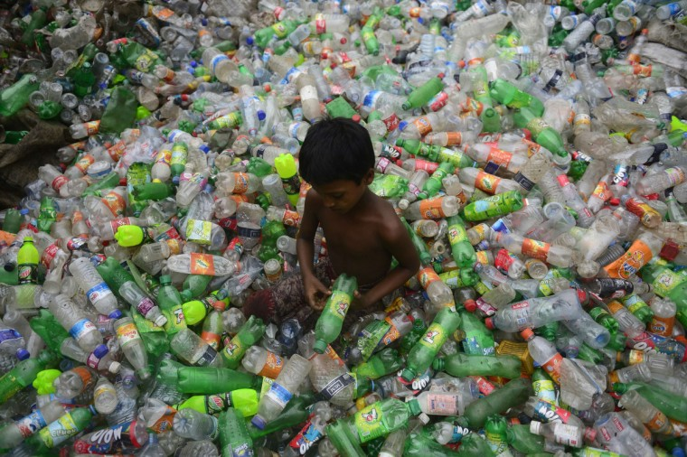 A Bangladeshi youth sorts through polyethylene terephthalate (PET) bottles for recycling in poor working conditions in Dhaka. PET bottle flakes are an exportable raw material from Bangladesh. The recycled material is used to produce PSF (Polyester staple fiber) which are then made into PSY (polyester spun yarn) or used as stuffing materials. (Munir uz Zaman/Getty Images)