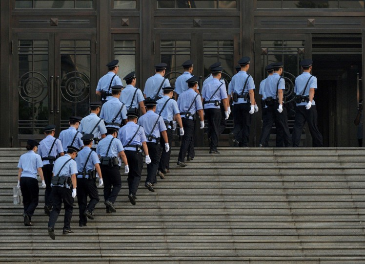 Police arrive at the Intermediate People's Court before disgraced politician Bo Xilai arrives for his trial in Jinan, Shandong Province. Once one of China's highest-flying politicians, Bo Xilai found himself in the criminal dock on trial for bribery and abuse of power in the country's highest-profile prosecution in decades. (Mark Ralston/Getty Images)