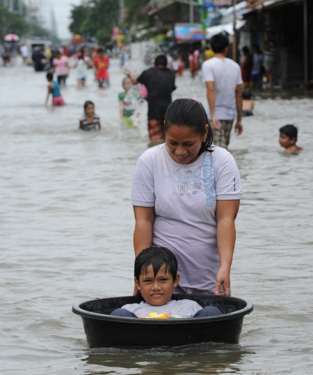A woman affected by flooding due to heavy rains exacerbated by Tropical storm Trami pushes a plastic basin with her son riding on it along a flooded street in the town of Calumpit, Bulacan province, north of Manila. (Ted Aljibe/Getty images)