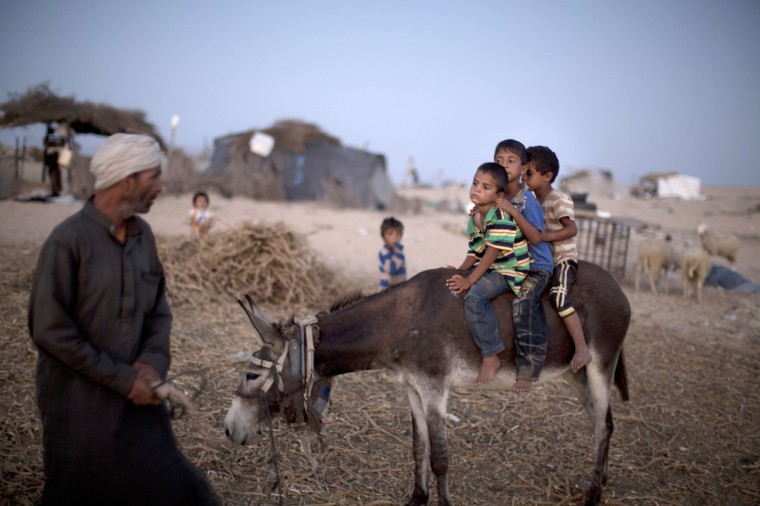 Palestinian children sit on a donkey in a poverty-stricken district of the town of Khan Younis where they live with their families in tents in the southern Gaza Strip. (Mahmud Hams/Getty Images)