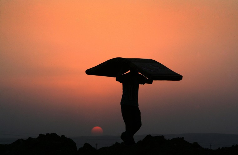 A Syrian-Kurdish refugee man carries a mattress at sunset at the Quru Gusik refugee camp, 20 kilometres east of Arbil, the capital of the autonomous Kurdish region of northern Iraq. More than 50,000 Syrian refugees have crossed into Iraq's Kurdish region in less than two weeks, an official said on August 26, 2013, as authorities rush to house them in more permanent camps. (Safin Hamed/Getty Images)