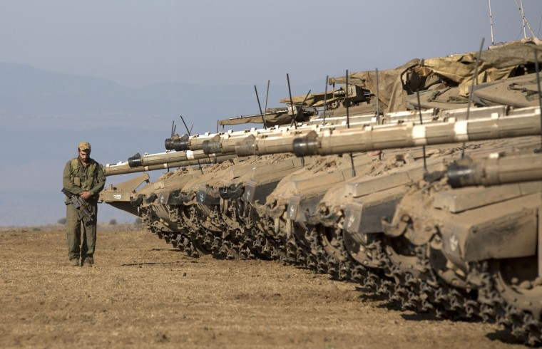 "An Israeli soldier walks next to Merkava tanks stationed in a deployment training area in the Israeli-annexed Golan Heights near the border with Syria. Israel will strike back ""fiercely"" if Syria attacks the Jewish state, Prime Minister Benjamin Netanyahu said, as the US mulled military action against President Bashar al-Assad's regime. (Menahem Kahana/Getty Images)"