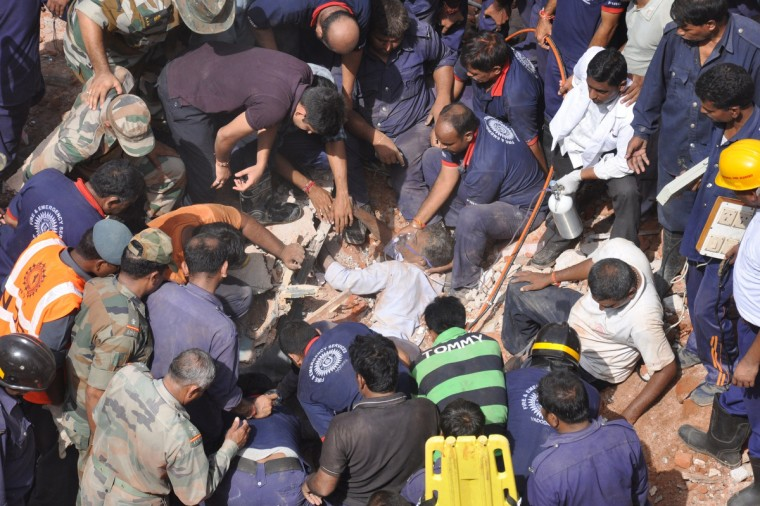 Indian rescue personnel administer oxygen to an injured man (C) trapped in the debris of a collapsed residential building near Vadodara, some 110 kms from Ahmedabad. Eleven residents were killed and another four injured and when the three-story residential building collapsed during pre-dawn hours. (Getty Images)