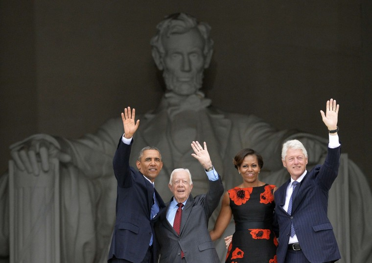 (L-R) US President Barack Obama, former president Jimmy Carter, First Lady Michelle Obama and Bill Clinton wave at the end of the Let Freedom Ring Commemoration and Call to Action to commemorate the 50th anniversary of the March on Washington for Jobs and Freedom at the Lincoln Memorial in Washington, DC on August 28, 2013. The March on Washington is best remembered for King's stirring vision of a United States free of inequality and prejudice, telecast live to a nation undergoing a phenomenal decade of soul- searching, crisis and change. (Jewel Samad/Getty Images)