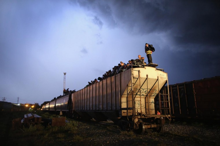 Central American immigrants wear plastic bags during a thunderstorm while atop a freight train about to head north early on August 4, 2013 in Arriaga, Mexico. (John Moore/Getty Images)