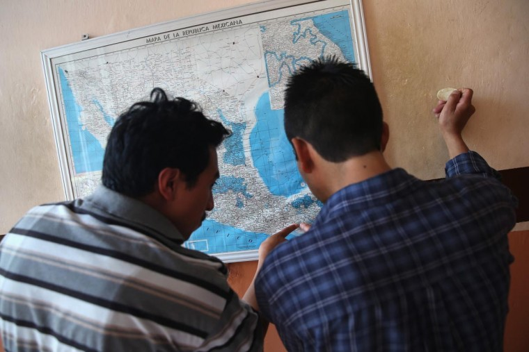 Central American immigrants check a map of Mexico before boarding a freight train headed north on August 3, 2013 in Arriaga, Mexico. Thousands of migrants ride atop the trains during their long and perilous journey through Mexico to the U.S. border. (John Moore/Getty Images)