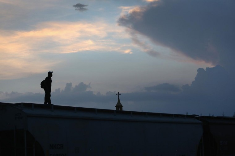A Central American immigrant stands atop a freight train about to head north early on August 3, 2013 in Arriaga, Mexico. (John Moore/Getty Images)