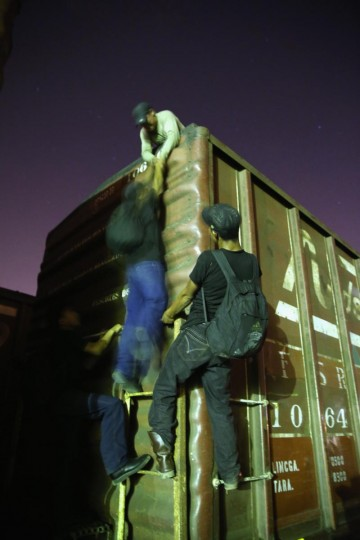 Central American immigrants climb atop a freight train headed north early on August 4, 2013 in Arriaga, Mexico. (John Moore/Getty Images)