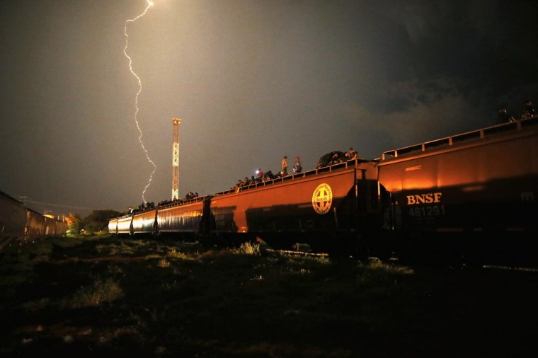 Central American migrants stand atop a freight train headed north early on August 4, 2013 in Arriaga, Mexico. (John Moore/Getty Images)