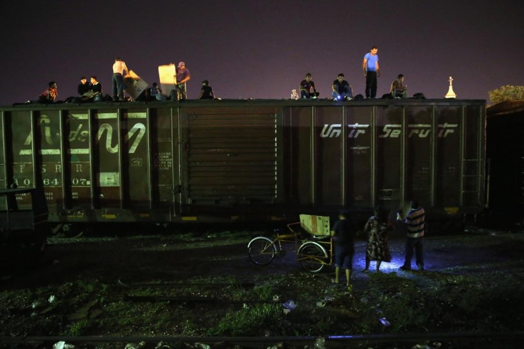 Central American immigrants sit atop a freight train about to head north early on August 4, 2013 in Arriaga, Mexico. (John Moore/Getty Images)