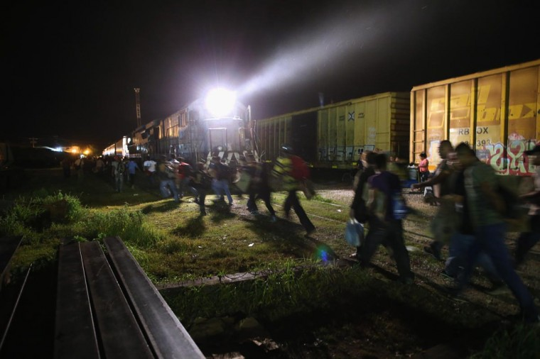 Central American migrants run to board a freight train headed north early on August 4, 2013 in Arriaga, Mexico. (John Moore/Getty Images)