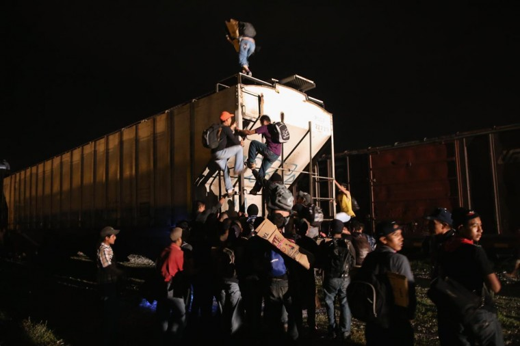 Central American migrants climb atop a freight train headed north early on August 4, 2013 in Arriaga, Mexico. (John Moore/Getty Images)