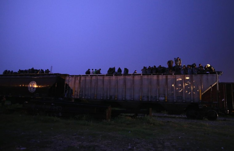 Central American immigrants wear plastic bags during a rain storm while atop a freight train about to head north early on August 4, 2013 in Arriaga, Mexico. (John Moore/Getty Images)
