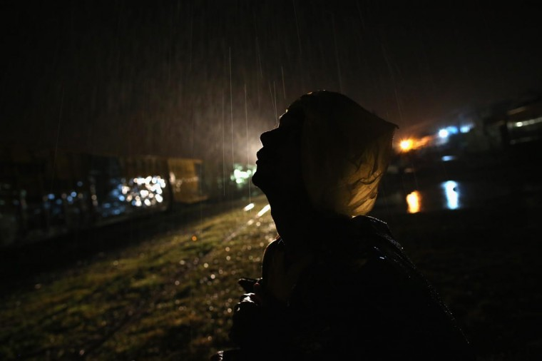 A Nicaraguan immigrant wears a plastic bag during a thunderstorm before climbing atop a freight train headed north early on August 4, 2013 in Arriaga, Mexico. (John Moore/Getty Images)