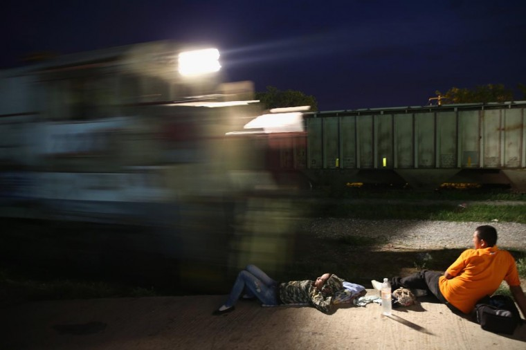 A Central American immigrants prepare to climb aboard a freight train headed north early on August 4, 2013 in Arriaga, Mexico. (John Moore/Getty Images)