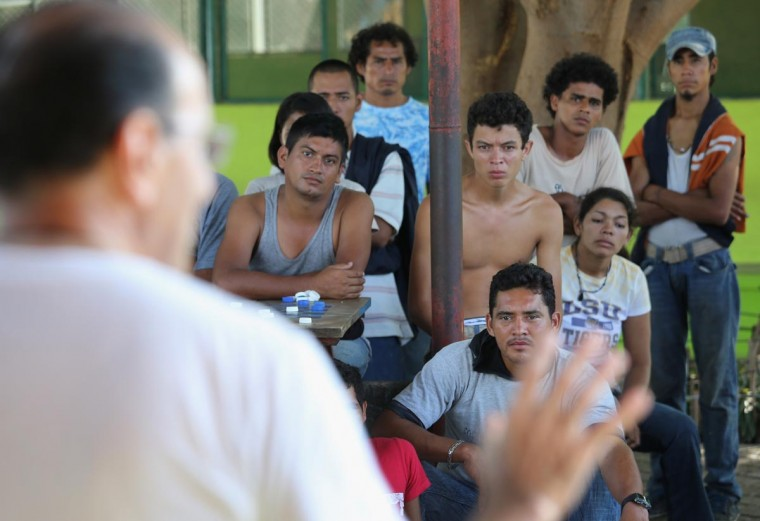 Migrants listen as Catholic Father Alejandro Solalinde Guerra warns them of the dangers in their journey to the United States, while at the Hermanos en el Camino (Brothers in the Road) shelter on August 4, 2013 in Ixtepec, Mexico. (John Moore/Getty Images)