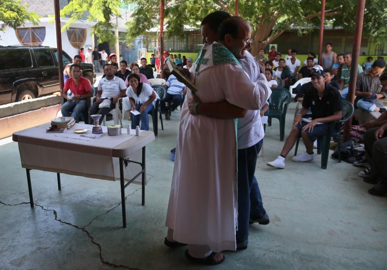 Catholic Father Alejandro Solalinde Guerra hugs a Cuban immigrant on his 42nd birthday following Mass at the Hermanos en el Camino (Brothers in the Road) shelter on August 4, 2013 in Ixtepec, Mexico. (John Moore/Getty Images)