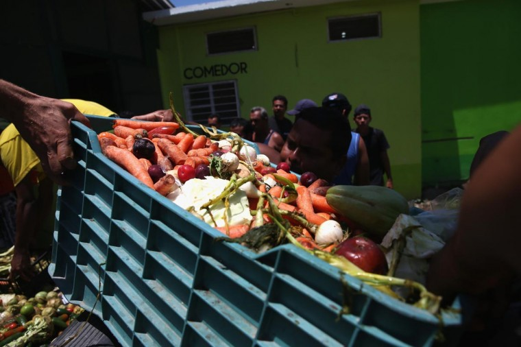Migrants unload donated vegetables and fruit at the Hermanos en el Camino (Brothers in the Road) shelter on August 4, 2013 in Ixtepec, Mexico. The shelter, founded by Solalinde Guerra in 2007, houses and feeds immigrants, mostly from Central America, at a train stop in their journey through Mexico towards the United States. (John Moore/Getty Images)